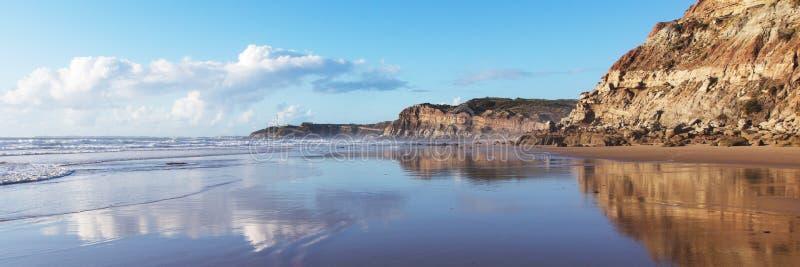 Berg in het vlotte water van het strand Areia Branca wordt weerspiegeld die Lourinha, Portugal, stock foto's