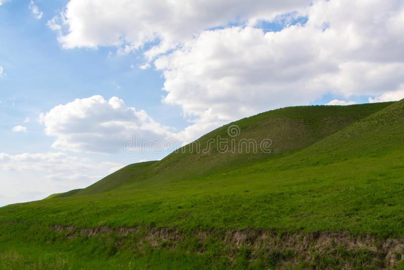 Berg, Himmel und flaumige Wolken lizenzfreie stockbilder