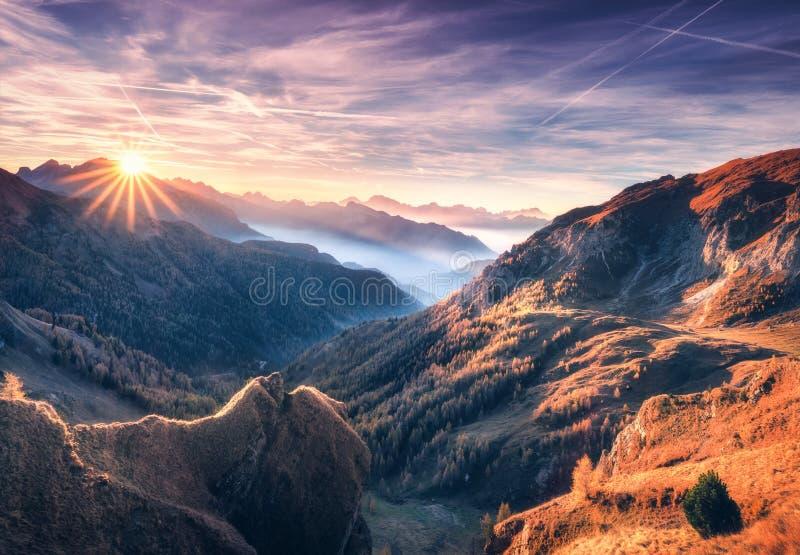 Berg i dimma p? den h?rliga solnedg?ngen i h?st arkivfoton
