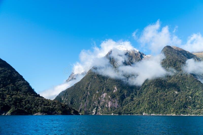 Berg i Milford Sound täckte vid det låga molnet arkivbild