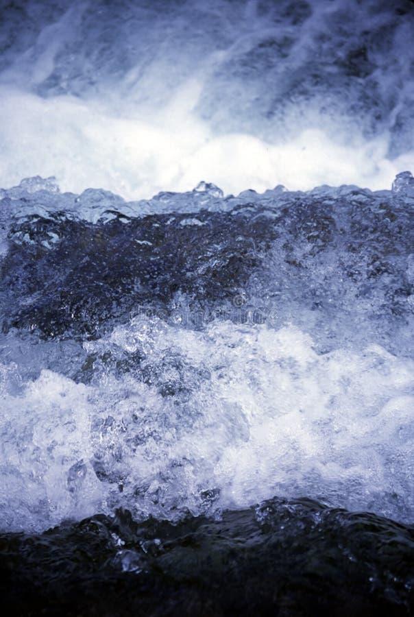 Berg meeslepende stroom, die tegen rotsen verpletteren royalty-vrije stock foto