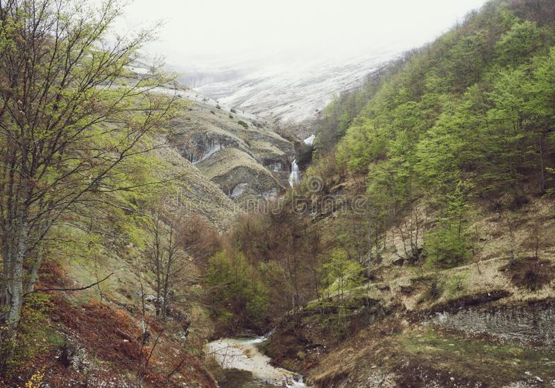 Berg met sneeuw en waterval in het bos van Montenegro royalty-vrije stock afbeeldingen