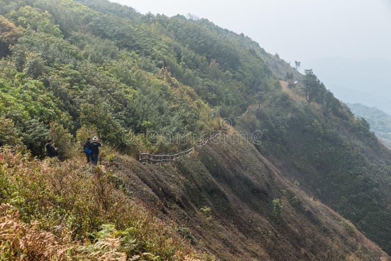 Berg mit Bahn zur anderen Seite mit vielen Bergen mit Nebel im Hintergrund bei Kew Mae Pan Mountain Ridge stockfotografie