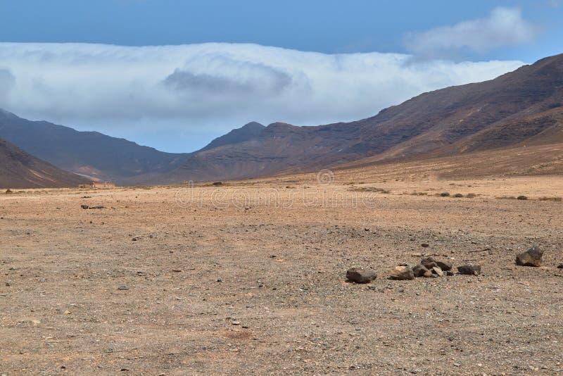 Berg mit braunen Wolken oben im Naturpark von Jandia in Fuerteventura lizenzfreies stockbild