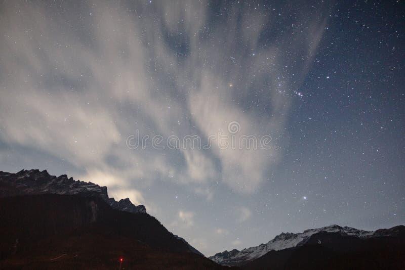 Berg mit wenigem Schnee auf die Oberseite und bewegliche Wolke in der blauen Farb-Nacht mit Sternen im Winter bei Lachung in Nord lizenzfreies stockfoto