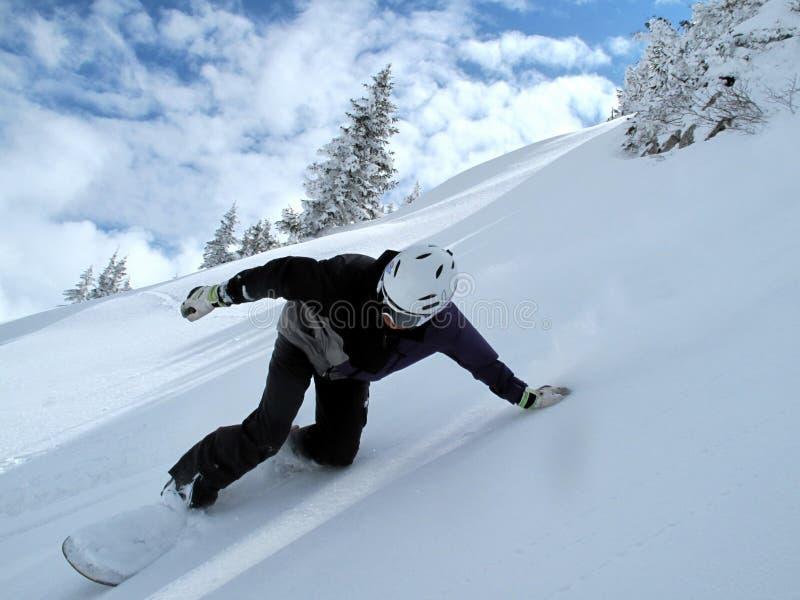 Berg mit Wolken und Schnee, Snowboarder in der vollen Geschwindigkeit lizenzfreies stockfoto