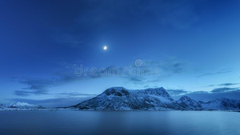 Berg mot blå himmel med moln och månen i vinter arkivbild