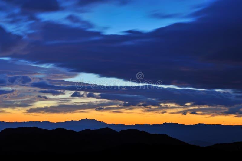Berg och moln på solnedgång royaltyfria foton