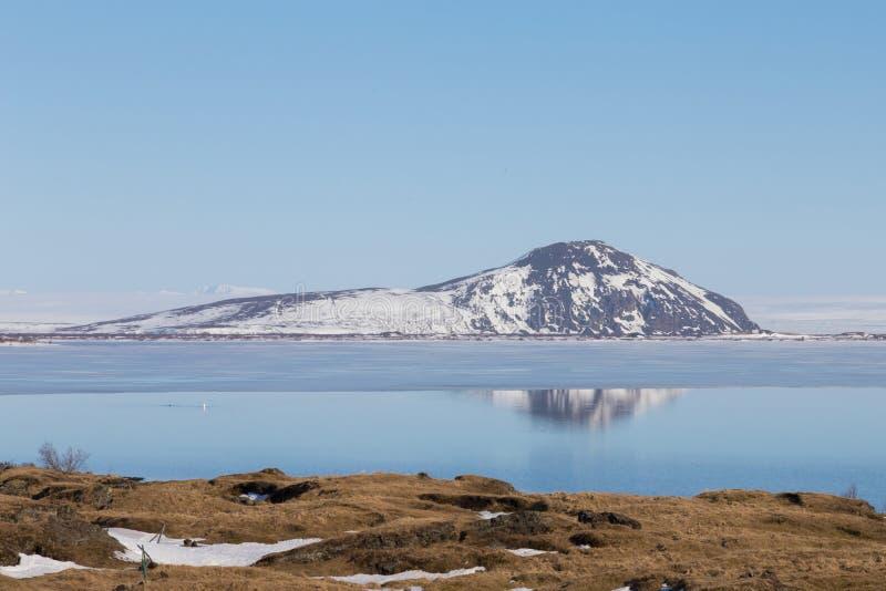 Berg och reflexion över sjön med klar bakgrund för blå himmel, Island arkivfoto