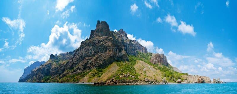 Berg op eiland in overzees stock foto