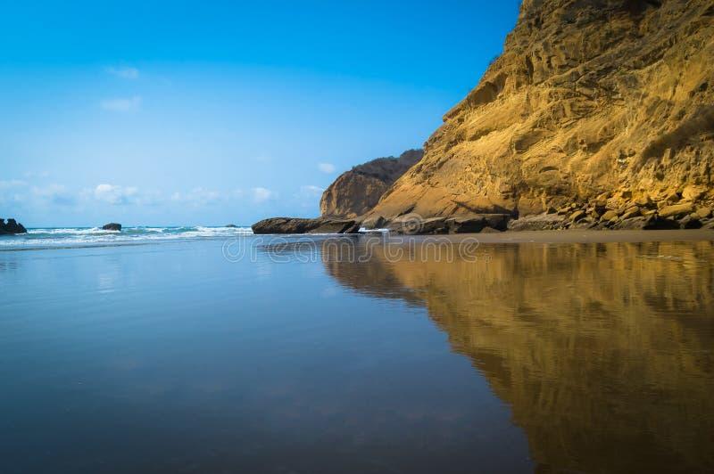 Berg reflekterade i havet arkivfoto