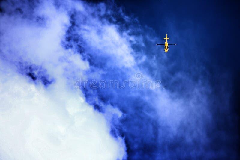 Berg-resue Hubschrauber, der im blauen Himmel hängt stockfoto
