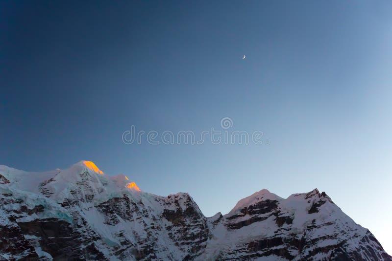 Berg Ridge för hög höjd och skymninghimmel med den unga månen arkivfoton