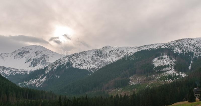 Berg Ridge med snö, solen och moln som är drivande vid stark vind royaltyfri foto