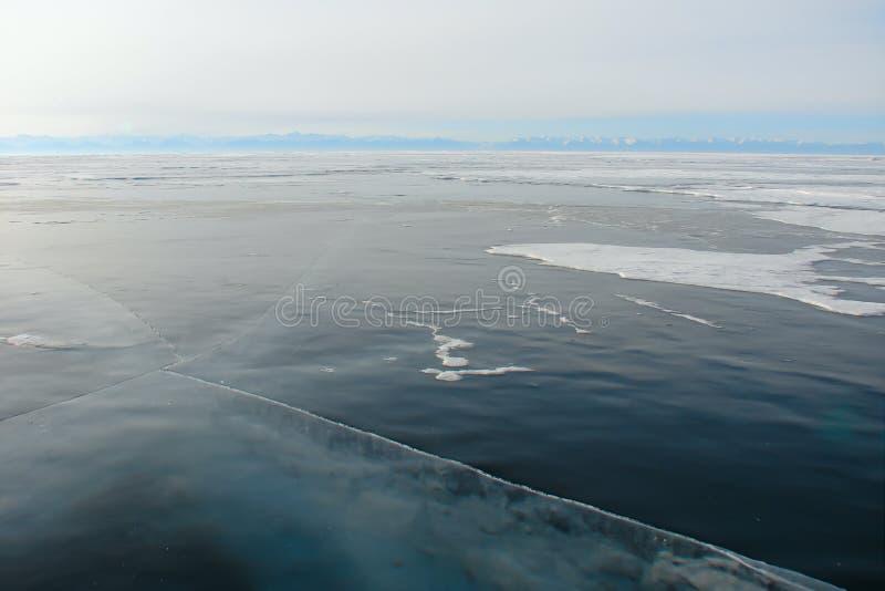 Berg sjö med tjockt mörkt - sprucken blå is igenom arkivfoto