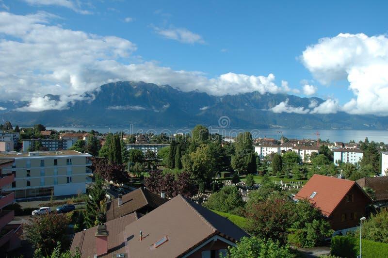 Berg, sjö och byggnader i La Turnera-de-Peilz i Schweiz royaltyfri bild