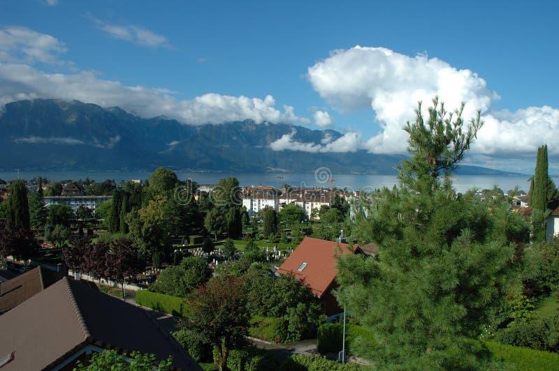 Berg, sjö och byggnader i La Turnera-de-Peilz i Schweiz arkivfoto
