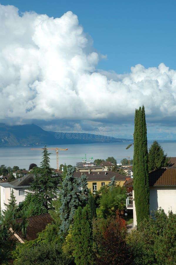 Berg, sjö och byggnader i La Turnera-de-Peilz i Schweiz fotografering för bildbyråer