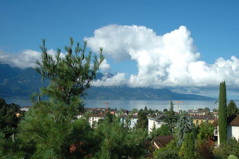 Berg, sjö och byggnader i La Turnera-de-Peilz i Schweiz arkivbilder
