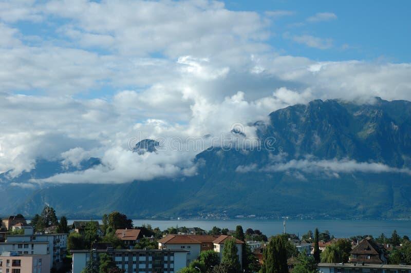 Berg, sjö och byggnader i La Turnera-de-Peilz i Schweiz royaltyfri fotografi
