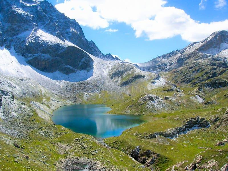 Berg sjö och första insnöat de schweiziska fjällängarna royaltyfri fotografi