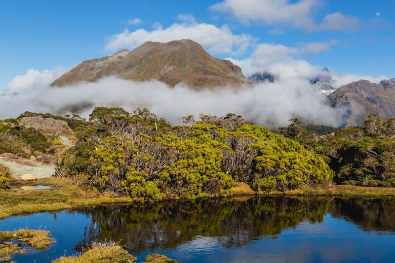 Berg sjö och moln, nyckel- toppmöteslinga, Routeburn spår, Nya Zeeland arkivbilder