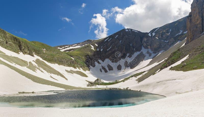 Berg sjö och snö arkivbild