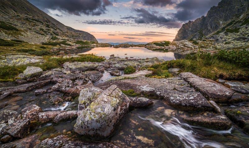 Berg sjön med vaggar i förgrund på solnedgången royaltyfria foton