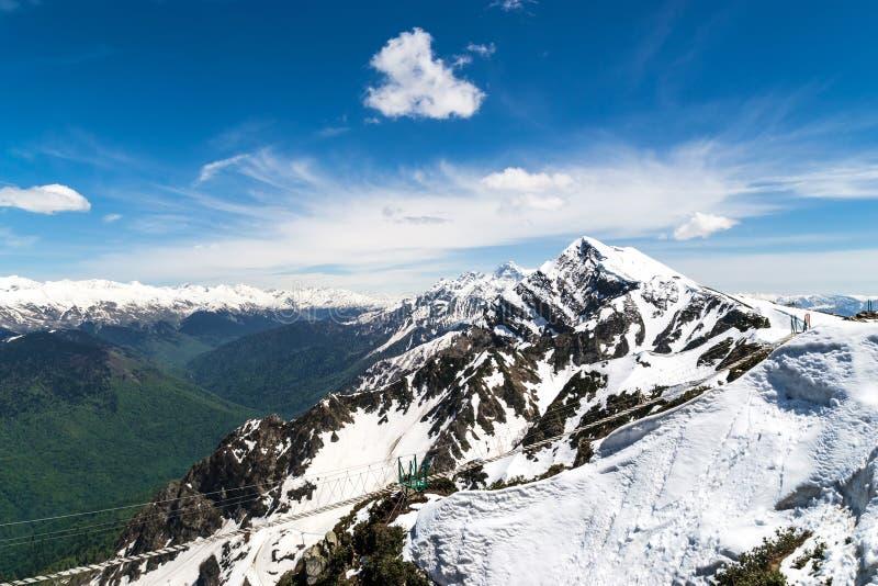 Berg sneeuwpieken met een brug die door de kloof gaan royalty-vrije stock foto