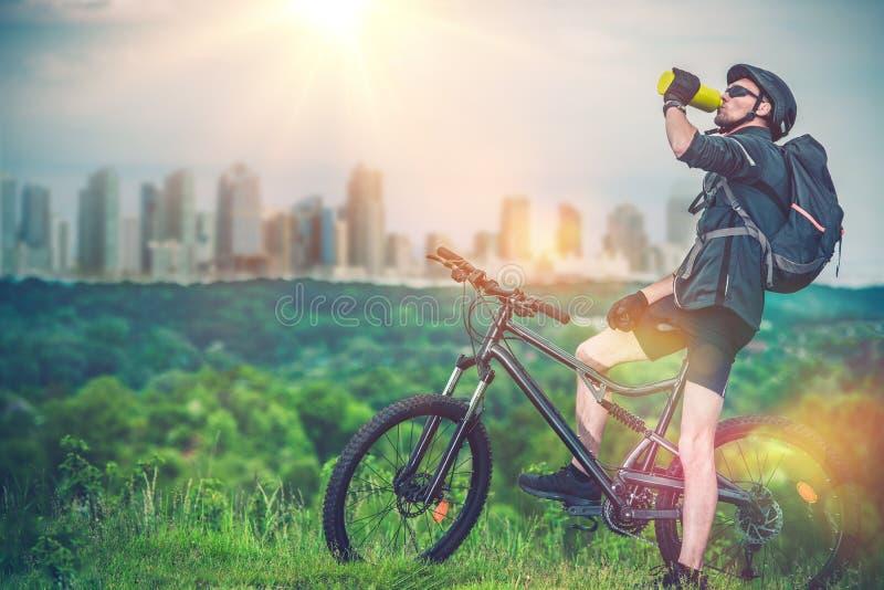 Berg som cyklar nära stad royaltyfri fotografi