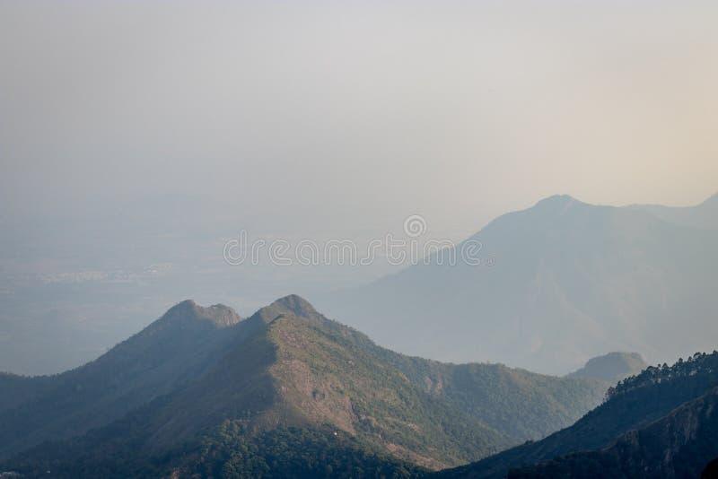 Berg som skuggar till horisonten för blå himmel arkivbild