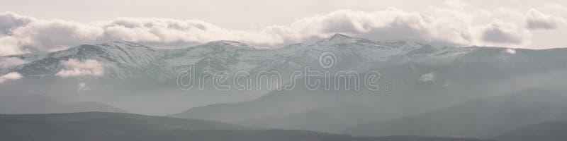 berg som t?ckas i vintersn? och l?ga moln med naket, vaggar arkivfoton