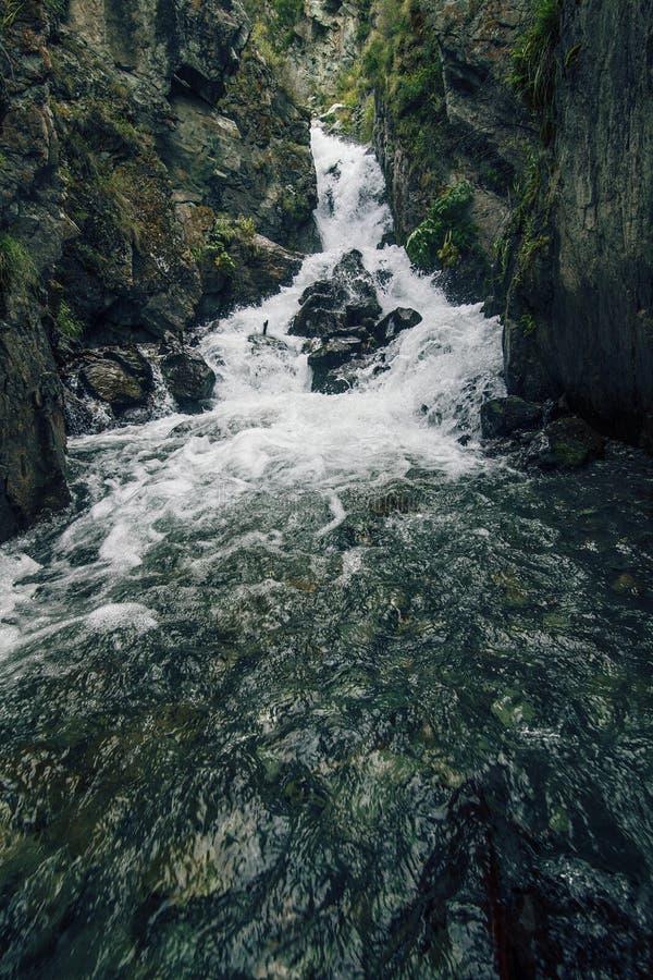 Berg toneel onbeschadigde waterval met ijswater die over stromen stock foto
