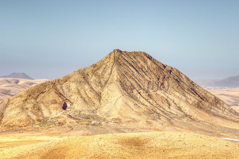 Berg tussen een dorp en het overzees royalty-vrije stock afbeelding