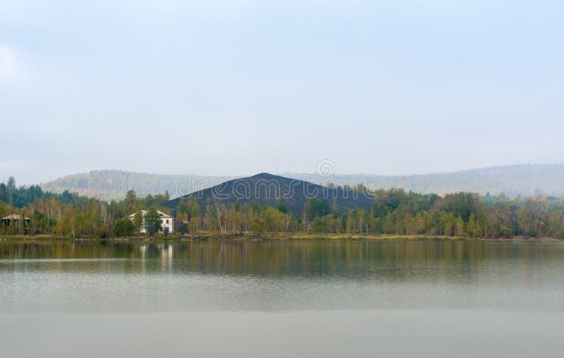 Berg van steenkool dichtbij het meer stock afbeelding