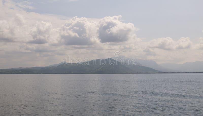 Berg vid havet under moln arkivbild