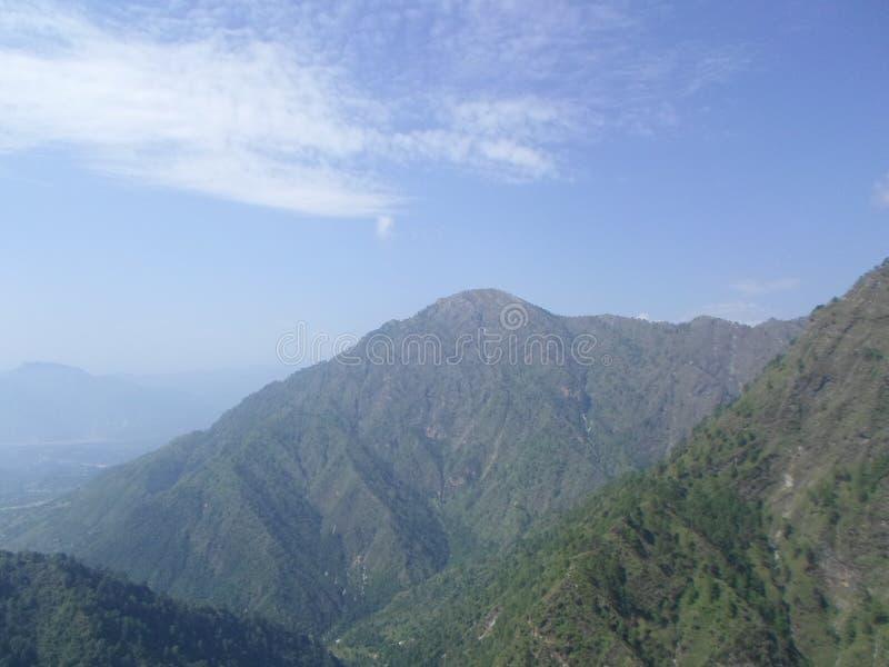 Berg wat betreft hemel stock afbeeldingen