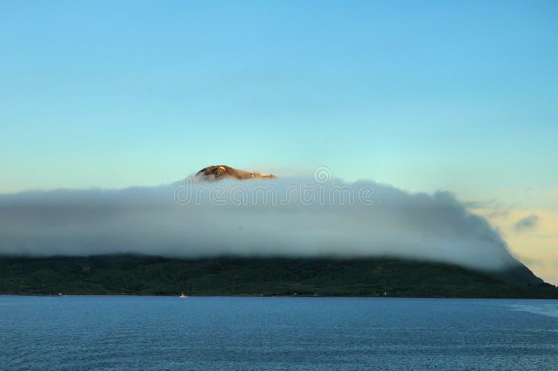 Bergachtige kust die met dichte wolken wordt behandeld stock foto