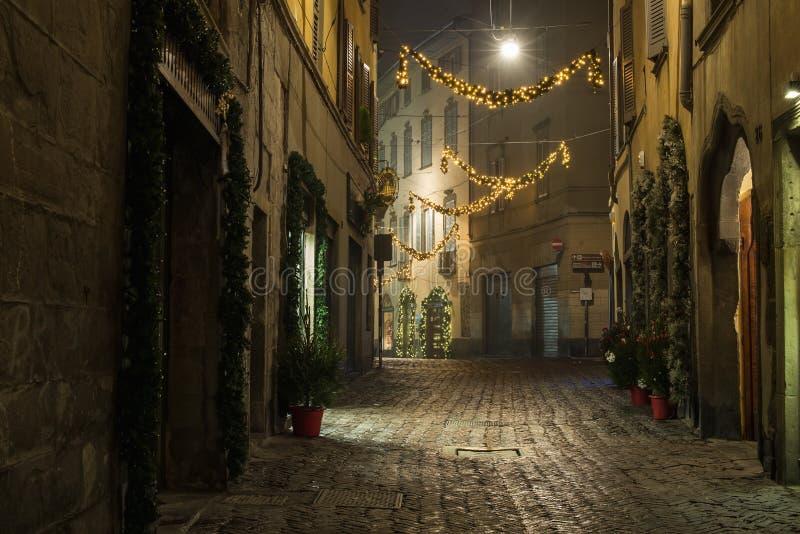 BERGAMO, ITÁLIA - 12, JANEIRO Rua vazia estreita europeia velha da cidade medieval com decoração do Natal em um nevoento imagens de stock