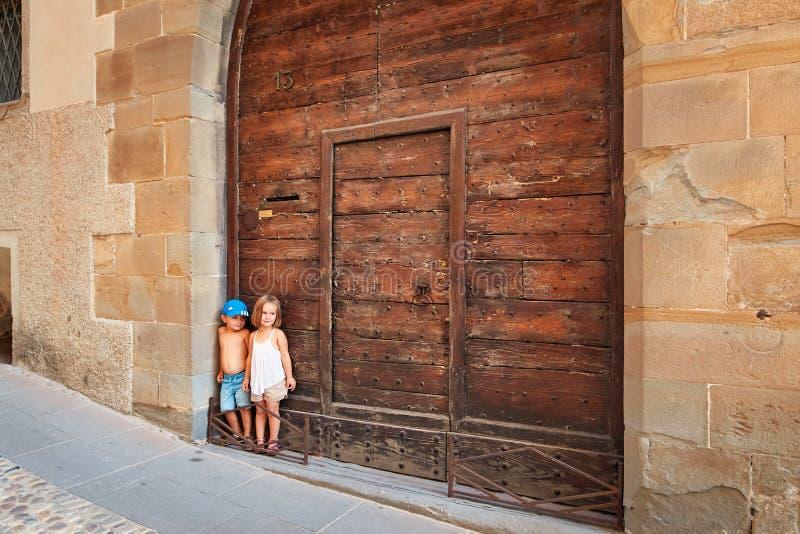 Bergamo Italien - Augusti 18, 2017: Konstiga barn står på portarna av deras hus fotografering för bildbyråer