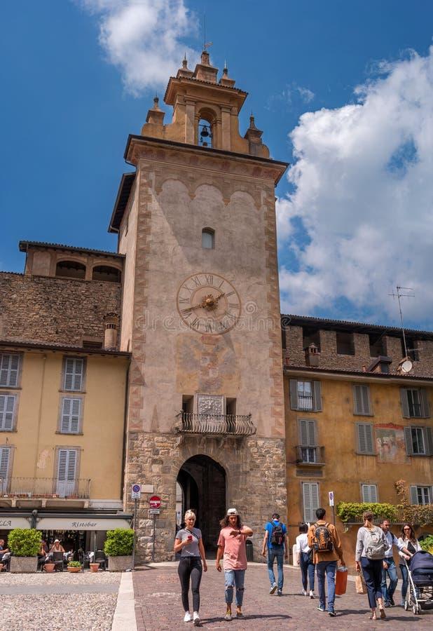 Bergamo, Italy - May 10, 2018: Bergamo clock tower. Torre Dell`Orologio in Piazza della Cittadella. Tourists on the stock photos