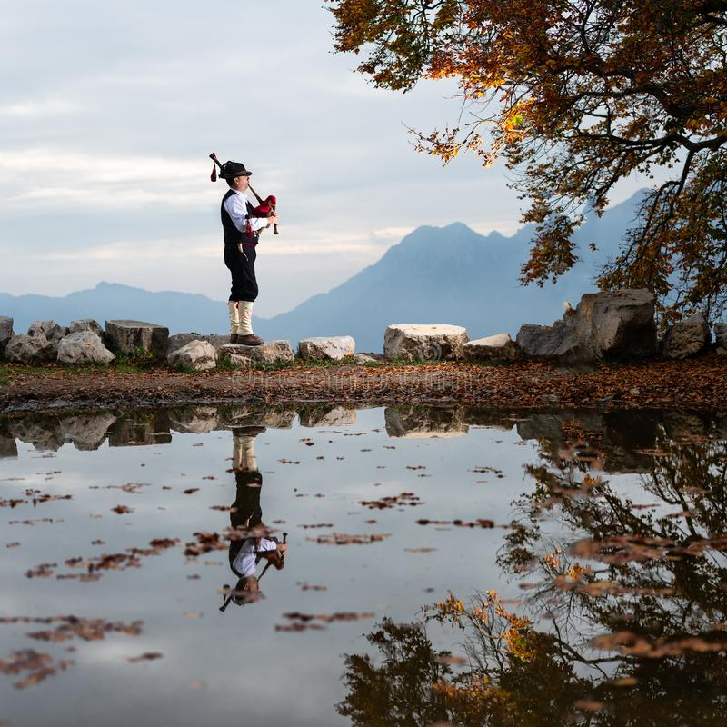 Bergamo player Bagpipe is reflected in a pool of water.  stock photo