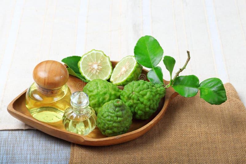 Bergamot with aromatic spa of bottles essential oil. Kaffir lime or bergamot with aromatic spa of bottles essential oil on sack background stock photography