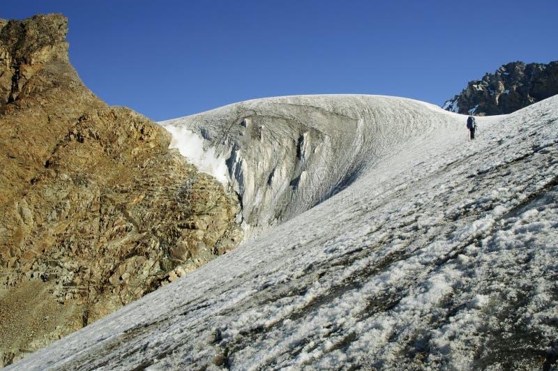 Bergbeklimmer die een gletsjer stijgt. stock foto's