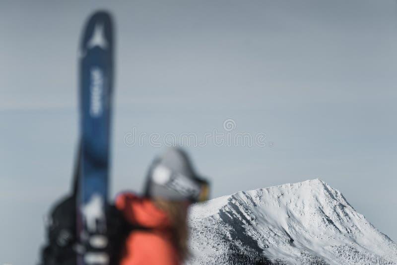 Bergbeklimmer die langs een sneeuwberg met de skis in de rugzak naar boven gaan Skiër op het het beklimmen spoor voor freeride-af stock afbeelding