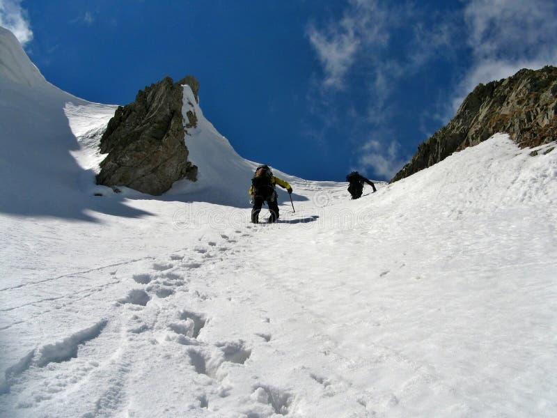 Bergbeklimmers die top stijgen stock foto