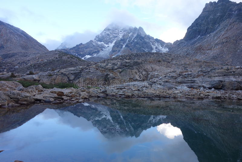 Bergbezinning in Water met wolken stock fotografie