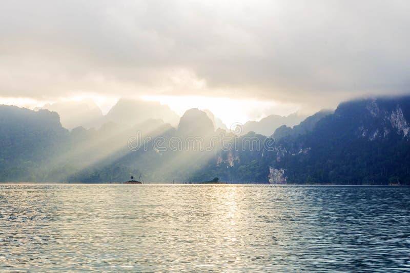 Bergblick mit See- und Sonnenstrahldurchlauf durch die Wolke stockbilder