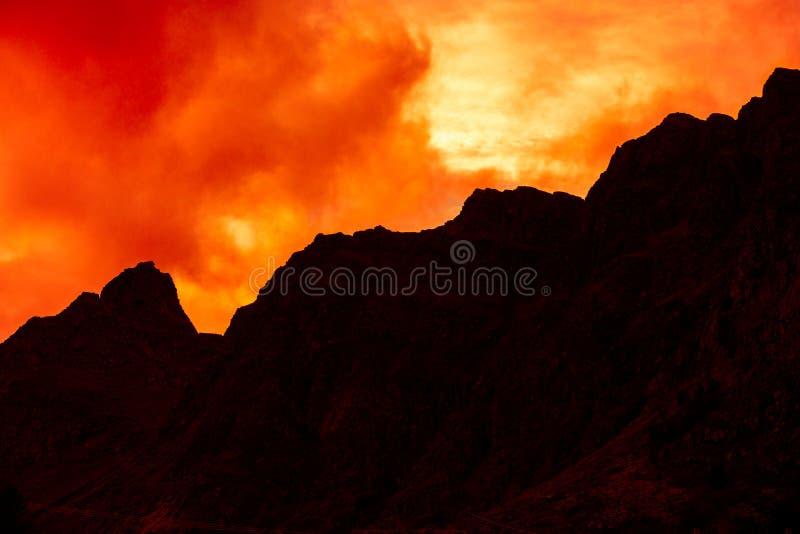 Bergbovenkant met bewolkte zonsonderganghemel die wordt geschetst royalty-vrije stock foto