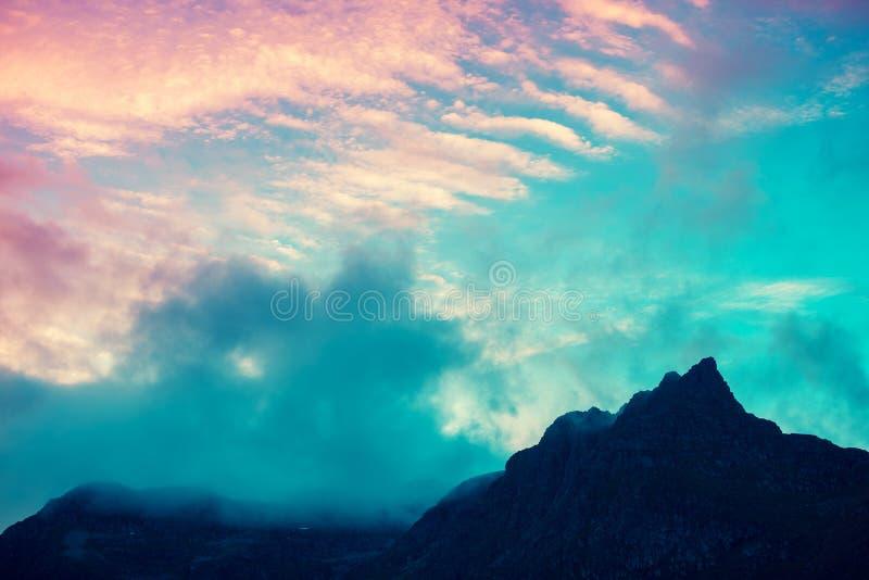 Bergbovenkant met bewolkte zonsonderganghemel die wordt geschetst stock afbeelding